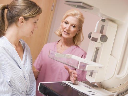 A nurse preparing a patient for her mammogram