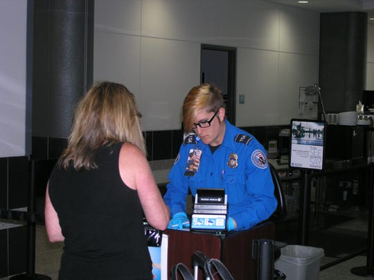 Melissa Hansen, transportation security officer for TSA, checks in a passenger Wednesday at Austin Straubel International Airport in Ashwaubenon. TSA is launching its PreCheck expedited screening program at the airport.