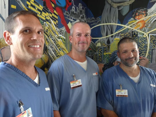 From left: Robert Feiss, Jason Brown and Rodney Lyle standing in front of the ceiling-to-floor wall murals that decorate the visitor room at the Wakulla Correctional Institution. They teach, paint and mentor fellow inmates through the Horizon Program.