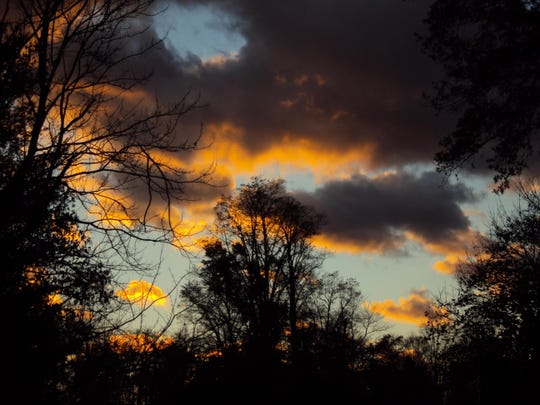 A sunset illuminates clouds hanging in the sky over Poughkeepsie.