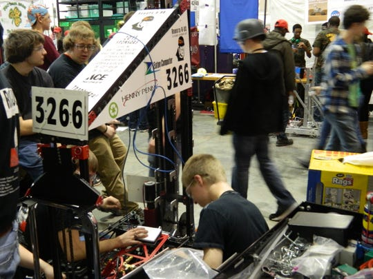 Members of Robots-R-Us work to solve one of many problems developed by their robot, Destiny, during the FIRST Robotics Competition regional last weekend in Perry, Ga.