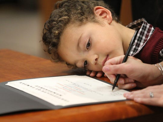 Jisaiah Conroy, 4, of Greece watches as his parents take turns signing his adoption paper.