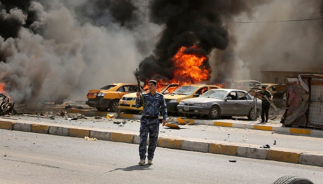 Iraqi policemen stand near burning vehicles moments after one in a series of bombs hit the Shiite stronghold of Sadr City, in Baghdad, May 13, 2014.