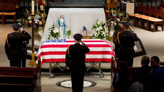 Omaha police officers salute before removing the flag from the top of the casket before the funeral service for Omaha police detective Kerrie Orozco on Tuesdya at St. John's Catholic Church at Creighton University in Omaha.