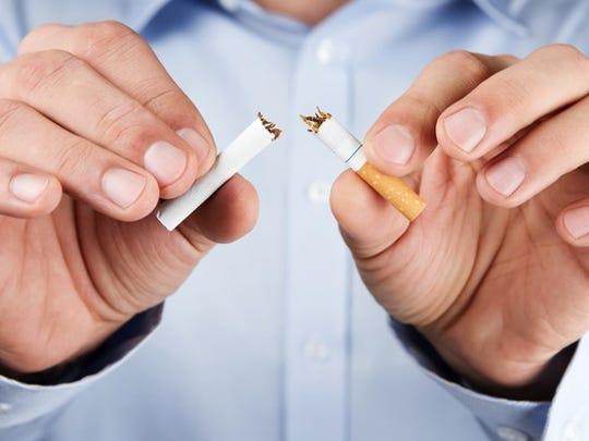 Man breaking a cigarette in half
