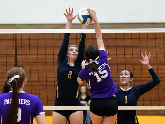 Dakota Valley's Anna Rasmussen goes up for the kill against Sioux Valley's Lynsey Stevens (2), while Bryn Tvedt (1) looks on.
