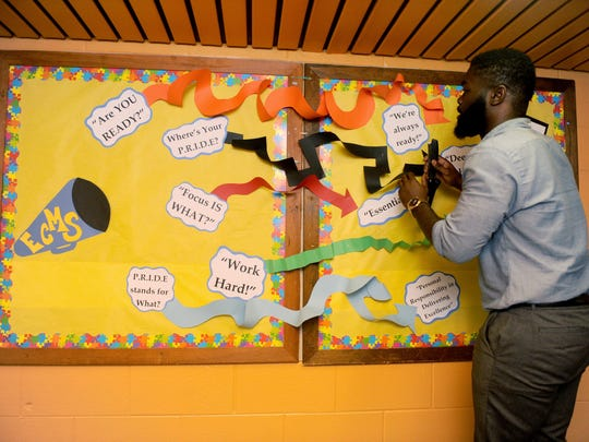 Principal Will Hayes put some final touches on school boards at the new renovated East Camden Middle School.