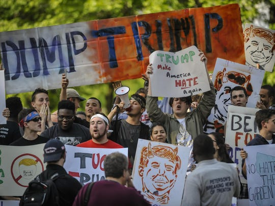 Demonstrators protest during a Trump rally in Lawrence,