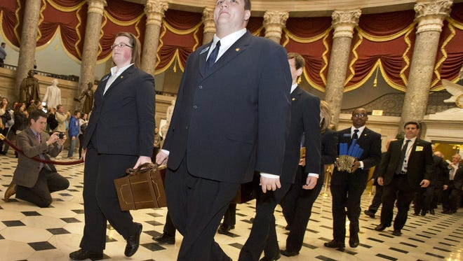 Pages carry boxes holding Electoral College votes to the House Chamber on Capitol Hill in Washington following the 2012 election.