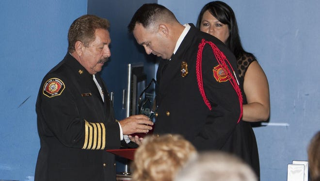 Peoria Fire Chief Bobby Ruiz presents the Firefighter of the Year award to Firefighter Troy Bauer.