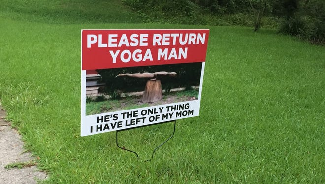 Amy Reiter has a sign in her front yard on Spottswood Drive. She wants whoever took her sculpture of Yoga Man to return it.