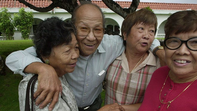 In this June 2002 file photo, Tiyan land heirs, from right, Lourdes Gutierrez, her sister Dolores Jesus Cruz, their brother, Roman Cruz, and his wife, Maria, congratulate each other after they were assured that the government will give their lands back.