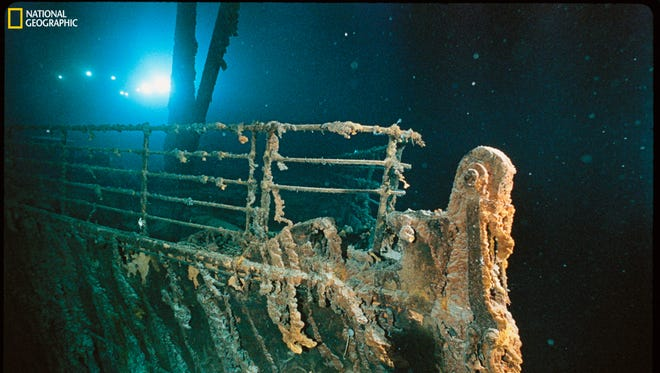 "Bow railing of R.M.S. Titanic illuminated by Mir 1 submersible behind the forward anchor crane. Rustcicles' slant shows the direction of the current. This photo is part of National Geographic's exhibition ""Titanic: The Untold Story."""