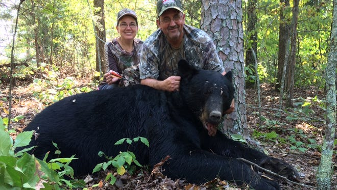 Kenneth Mize, husband of Baxter County Treasurer Jenay Mize (left), shows off a monster bear he took with a crossbow on Oct. 1, opening day of archery season for bear in Arkansas. The bear, taken in the Jordan area, measured 6 feet, 5.5 inches nose to tail, had a green skull size of 21 3/8 inches and weighed well over 400 pounds. The bear was the first of Mize's career.