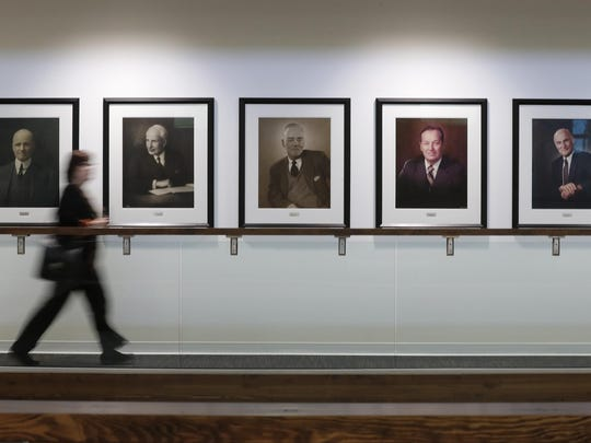 A visitor walks past the wall of presidents as part of a tour Sept. 7 at Menasha Corporation's new headquarters in Neenah.