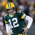 Packers quarterback Aaron Rodgers makes his championship-belt gesture after throwing a touchdown pass.