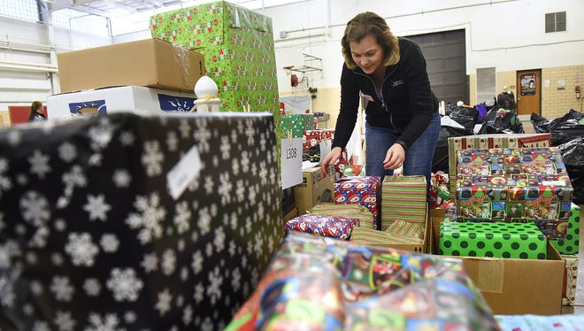 Volunteer Susan Pauly prepares gifts for distribution as part of the Share the Spirit program Thursday, Dec. 10, 2015, at the St. Cloud Armory. Volunteer Susan Pauly prepares gifts for distribution as part of the Share the Spirit program Dec. 10, 2015, at the St. Cloud Armory.