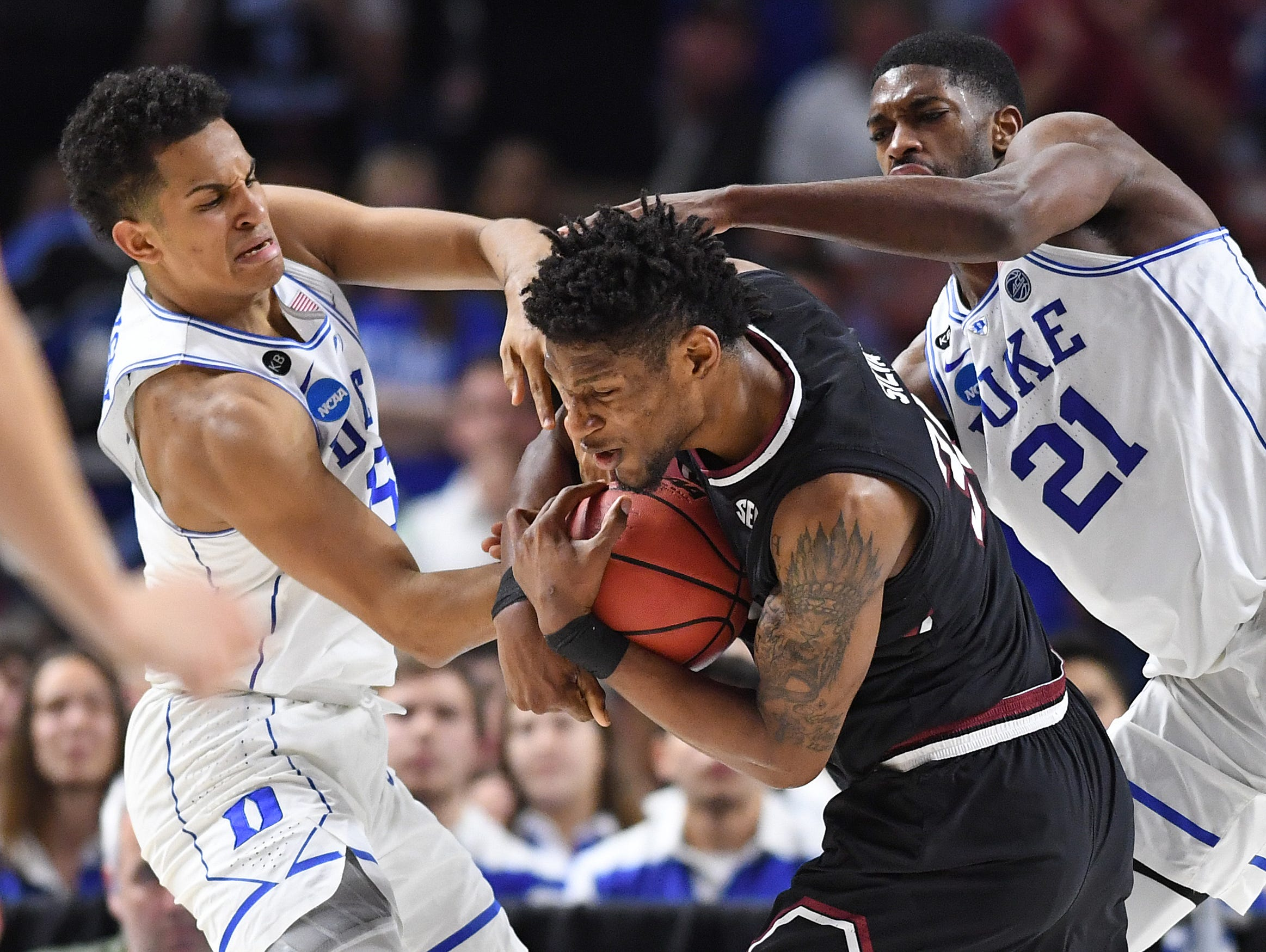 South Carolina forward Chris Silva (30) pulls down a rebound between Duke guard Frank Jackson (15), left, and forward Amile Jefferson (21) during the 2nd round of the NCAA Tournament at Bon Secours Wellness Arena in downtown Greenville on Sunday, March 19, 2017.