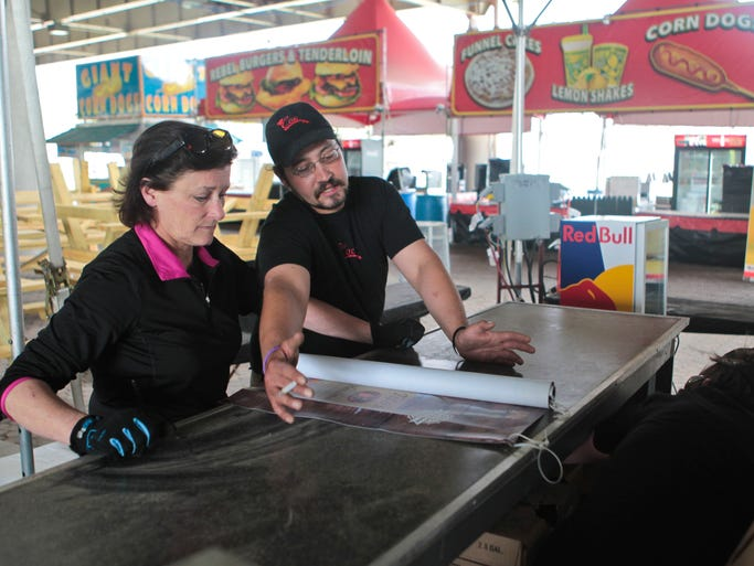 Lori Cox, left, and Kyle Johnson of Concessions by Cox,  Inc. discuss the way to set up a bar in preparation for the Kroger Fest-A-Ville that's part of the Derby Festival Chow Wagon that opens Thursday.  April 22, 2014