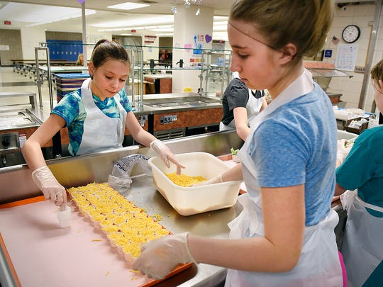 Ellie Oehrlein, 12, (left) and Evelyn Eich, 11, volunteer Thursday, Feb. 11, to help the kitchen staff get ready for lunch at Clearview Elementary School, Clear Lake.