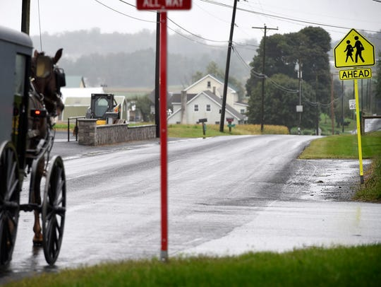 Amish buggies pass by the New Hope Amish School Wednesday,