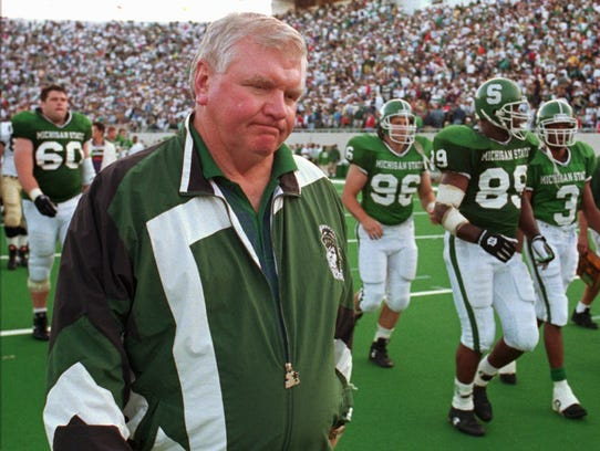 Michigan State football coach George Perles walks off