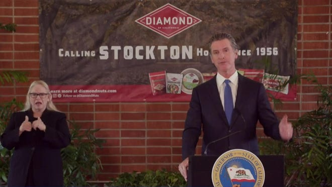 In this image from his livestreamed news conference from Stockton's Diamond Nuts, Gov. Gavin Newsom announces new efforts Monday focusing on supporting the Central Valley, a region seeing concerning virus spread that is disproportionately impacting Latinos.