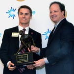 Mississippi State freshman outfielder Jake Mangum, left, is presented the Ferriss Trophy by Hu Meena, president and CEO of C Spire Wireless Monday in Cleveland.