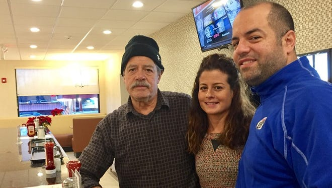 Tony Exadaktilos Sr., left; his daughter Marianne and son Tony Jr., stand at the counter of the family's newly rebuilt Crystal Lake Diner.