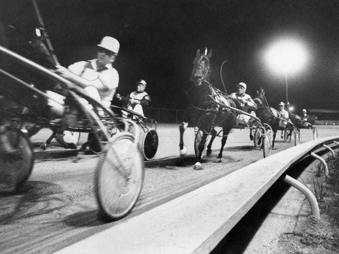 Tenseness shows on the driver's facees as a closely-bunched field heads into one of the turns at Louisville Downs harnes track.  Aug. 22, 1969 -