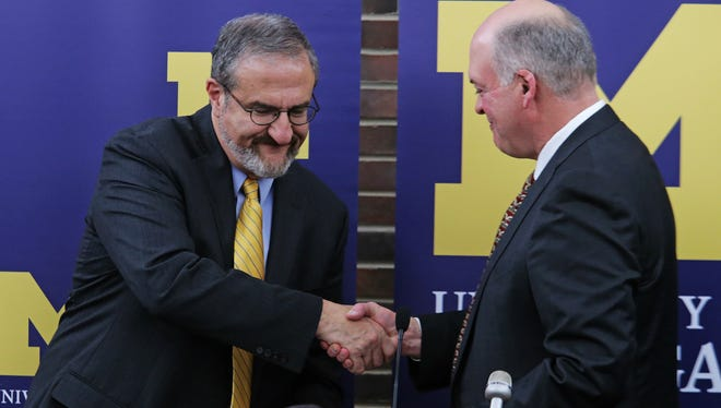 University of Michigan President Mark Schlissel, left, shakes the hand of interim Athletic Director Jim Hackett after announcing the resignation of University of Michigan Athletic Director Dave Brandon at the Regents' Room of the Fleming Administration Buildingon Friday October 31, 2014 at the Ann Arbor campus.