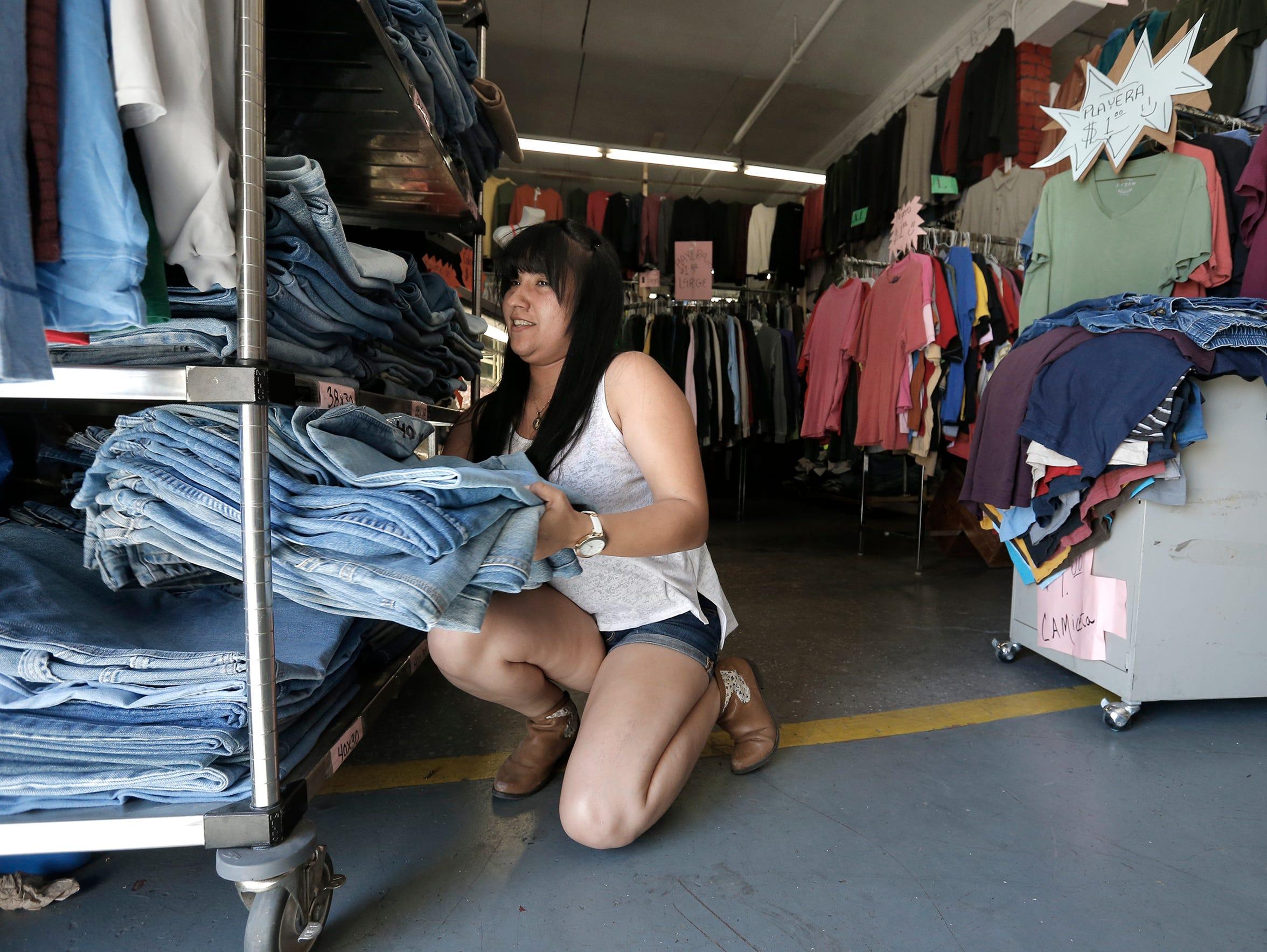 Carla Ocon arranges jeans at her shop inside El Tiradero