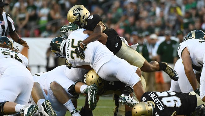 Colorado safety Tedric Thompson (top) stops Colorado State running back Izzy Matthews in a game last season.