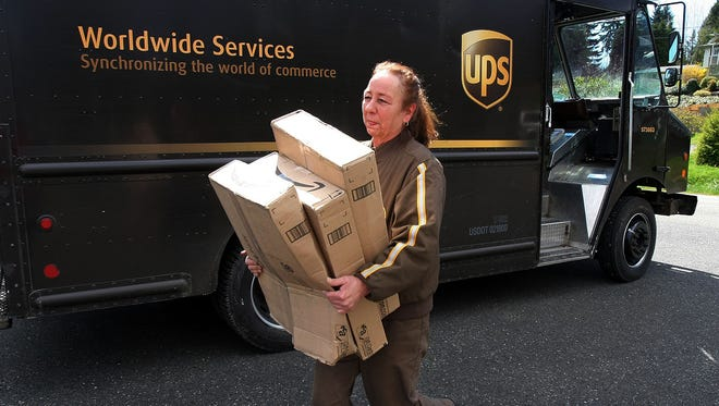UPS driver Peggy Larson carries packages during her route in Manchester, Wash., in this photo from April 2013.