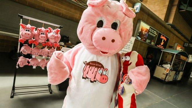 A pork mascot greets customers at the Bacon Bites boot