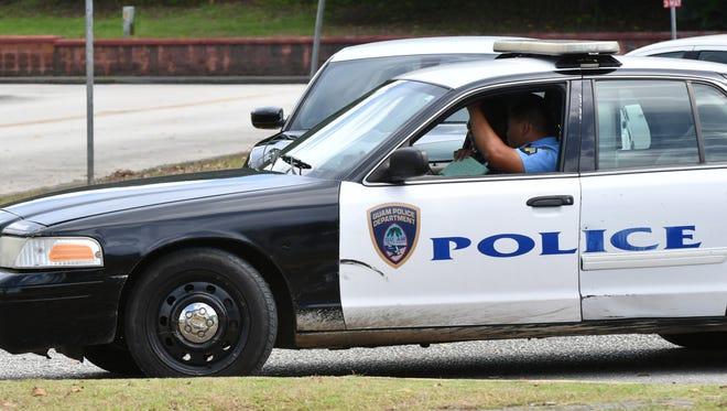 Guam Police Department officers exit a precinct.