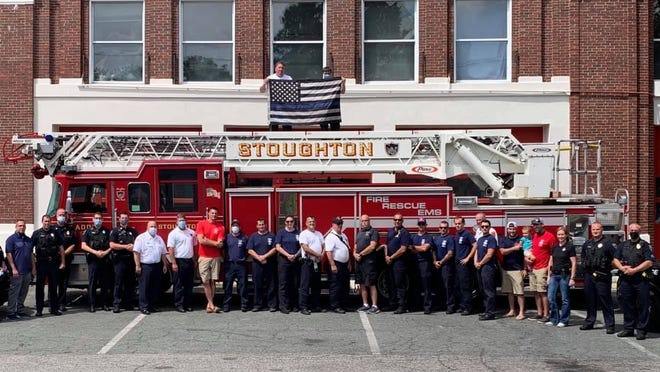Members of the Stoughton police and fire departments pose with the thin blue line flag touring Massachusetts after it was removed from a Hingham fire truck in July. The photo was taken in front of a Stoughton Fire Department ladder truck at the Freeman Street fire station, Tuesday, Aug. 25, 2020.