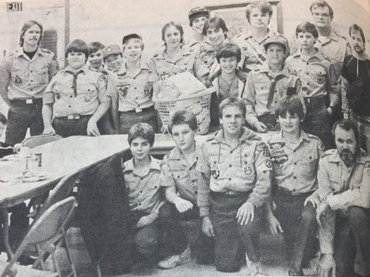 Members of Boy Scout Troop 27 pose with their leaders and the food basket they donated to a needy family in the area in December 1985.