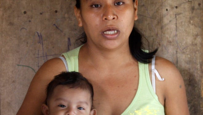 In this Wednesday, Feb. 12, 2014, photo, Irma Lopez, holding her son Sabino Slavador, talks during a interview in her house in San Felipe Jalapa de Diaz, Mexico.