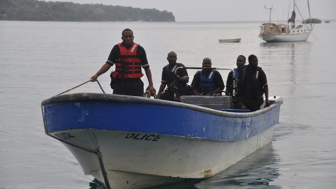 Jamaican Marine Police return to the Port Antonio Marina after searching for the Glazers' plane, which crashed Friday.