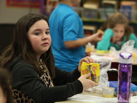 Alina Pullen, a fourth grader at Gates Chili's Neil Armstrong Elementary School, finishes up her breakfast at her desk.