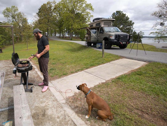 Joe Hawley cooks steaks for lunch with his dog Freedom