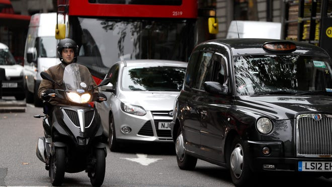 Vehicles drive in central London, Wednesday, July 26, 2017. To control air pollution, new diesel and petrol cars and vans could be banned in the UK from 2040. (AP Photo/Kirsty Wigglesworth)