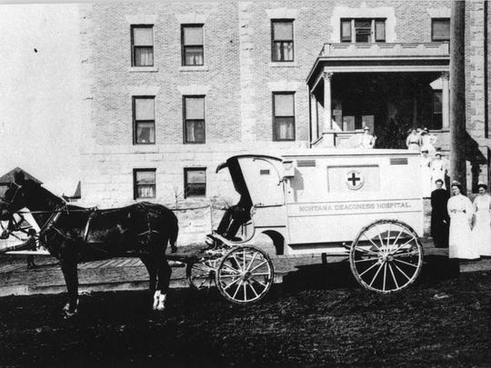 Nurses pose with a horse-drawn ambulance outside the