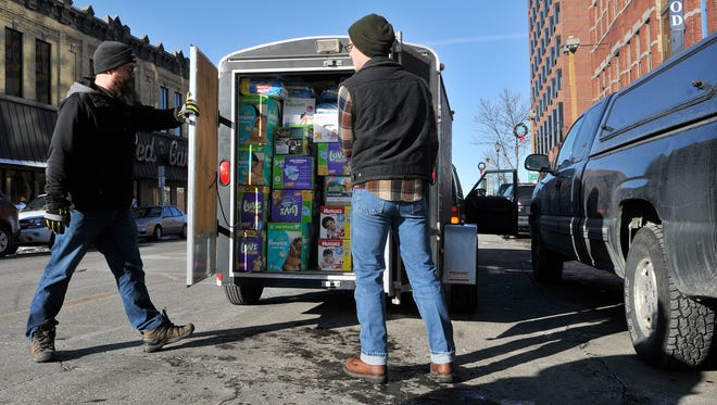 Tom Imholte, left, and Sean Rasmussen, both of St. Cloud, close up a trailer full of diapers collected Monday, Jan. 4, 2015, from Pioneer Place. Operation Baby New Year collections from about 20 sites netted 104,527 diapers, which will be distributed to local nonprofits.