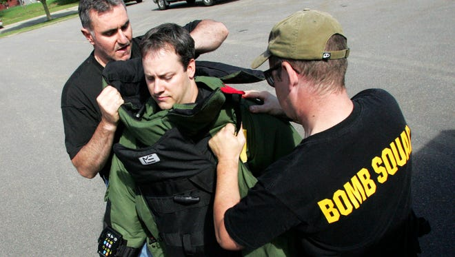 Oneida County Bomb Technician Jack Lemke, left, and Marathon County Bomb Technician Tim Krohn, right, help Marshfield Police Officer Pat Zeps, center, put on a bomb suit in this file photo.