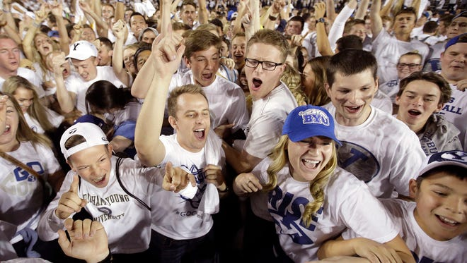 This Sept. 12, 2015, file photo, BYU fans celebrate their victory over Boise State in an NCAA college football game in Provo, Utah. Some of Utah's most influential Mormons, including Mitt Romney, Gov. Gary Herbert and the president of the Utah Jazz, are lobbying to get the private, Mormon church-owned Brigham Young University an invitation to join the lucrative Big 12 athletic conference.