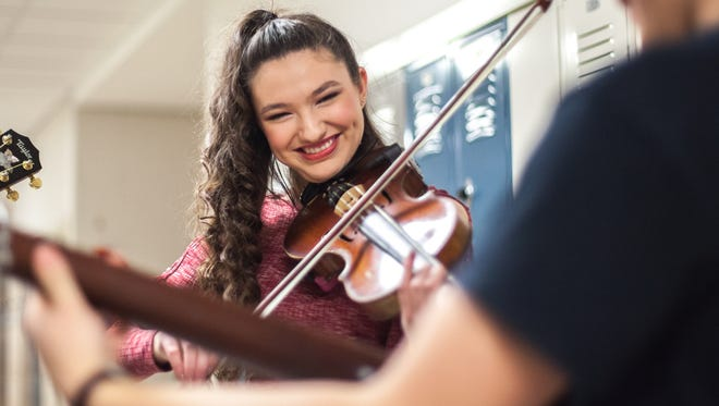 14-year-old Ivy Phillips plays with a group of fellow musicians in the hallway before going on to perform at the 43rd annual Old-Time Fiddlers' championships on Saturday, March 11, 2017.