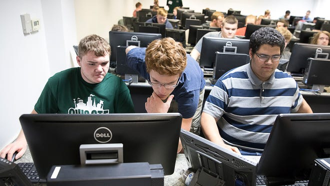 Chillicothe senior Clark Coulter, middle, helps fellow teammates Chad Park, left, and Austin Taynor, right, with a cybersecurity scenario at Ohio University Chillicothe on Tuesday, May 1, 2018.