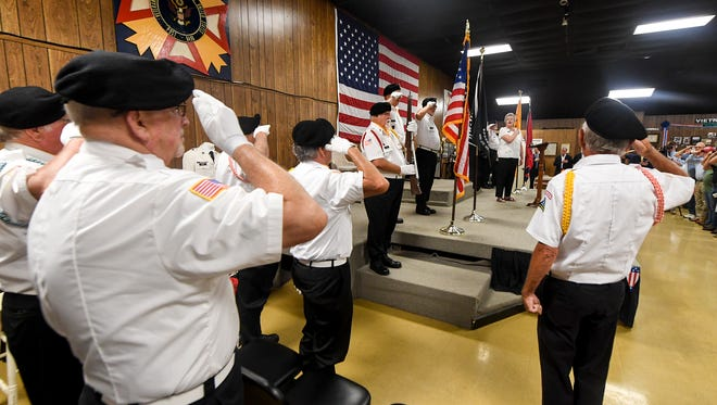 Members of the Vietnam Veterans of America 995 Honor Guard salute the American Flag during the singing of the National Anthem during the Vietnam Veterans Memorial Bridge renaming program, Tuesday, July 31, at the VFW 6496.